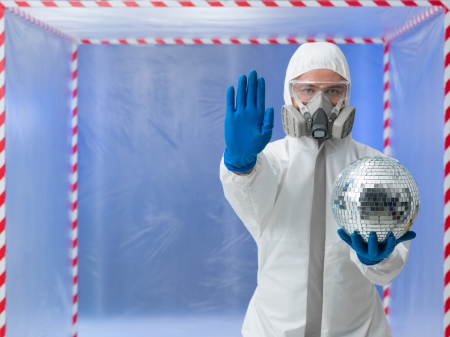 halt: person dressed in a bio hazard protective suit making a halt gesture with one hand and holding a disco ball in the other in front of a confinement tent
