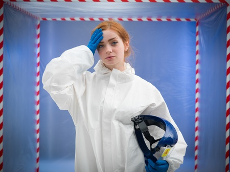 redheaded woman in protective white suit holding a protective helmet in one hand and wiping her forehead with the other Stock Photo - 20691535