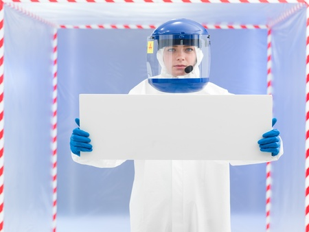 advisement: person in protective suit and helmet presenting a white board with both arms in front of a confinement tent
