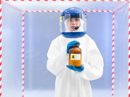 biologist: Person in a biohazard suit with a toxic substance in a brown bottle labelled as a poison held in her hands