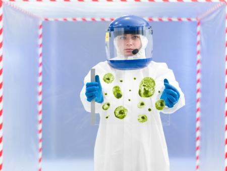 specimen testing: persona con traje protector sosteniendo muestras de microorganismos en una l�mina de vidrio en frente de una tienda de contenci�n Foto de archivo