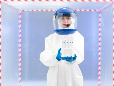 containment: person in biohaard protective suit holding a tube rack filled with test tubes containing a trasparent colorless liquid marked as bio hazardous in front of a containment tent Stock Photo