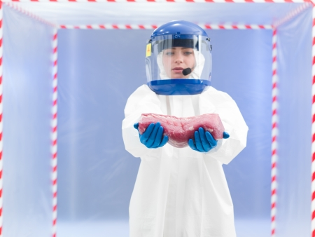 containment: person in biohazard suit calling holding a chunk of raw meat with both hands in front of a containment tent