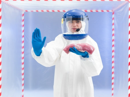 suspected: Woman in a biohazard suit with a meat sample in her gloved hand holding up her other hand in a gesture to stop indicating that there is a suspected chemical, bacterial or viral contamination