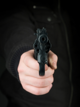 defendant: closeup of the hand of a person dressed in black, pointing a gun towards the viewer Stock Photo
