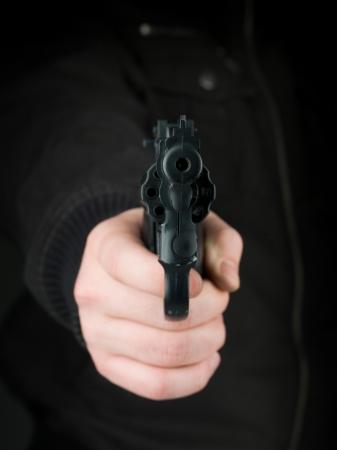 delincuencia: Primer plano de la mano de una persona vestida de negro, apuntando un arma hacia el espectador