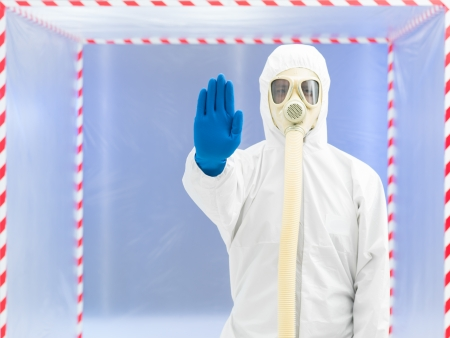 halt: person wearing a protective suit and gas mask calling a halt in front of a confinement tent Stock Photo