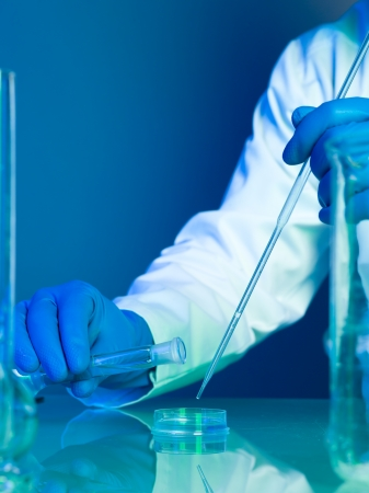 didactic: person wearing a white lab coat and blue rubber gloves pouring a blue substance in a petri dish and mixing it with drops of transparent liquid from a pipette on a reflective surface
