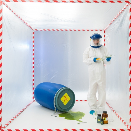 containment: Biohazard scientist in a full biohazard suit and helmet testing a green chemical spillage from an overturned drum inside an isolation or containment tent Stock Photo