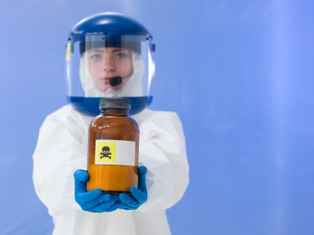virus protection: close-up of female scientist wearing white protection suit and mask holding a bottle labeled with deadly sign, on blue background Stock Photo