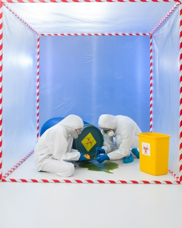 savant: specialists wearind white protection suits and gas masks collecting samples from a liquid spilling from a blue biohazard barrel, in a cube surrounded by red and white tape