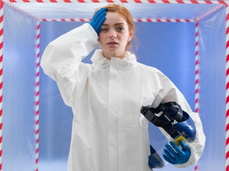 sterilization: Exhausted or infected female biohazard scientist dressed in a biohazard suit holding her helmet mask in one hand and her forehead with the other