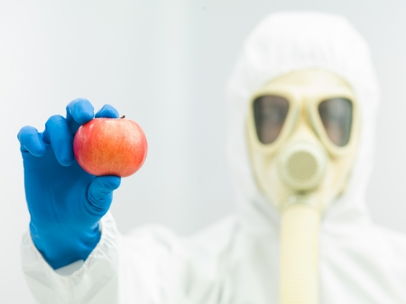 specimen testing: person in protective suit and gas mask holding a ripe red apple