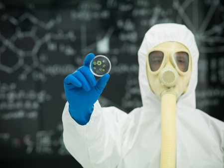 person in protective gear with gas mask holding a microorganism specimen in front of a blackboard  with graphics and formulas written on it in chalk