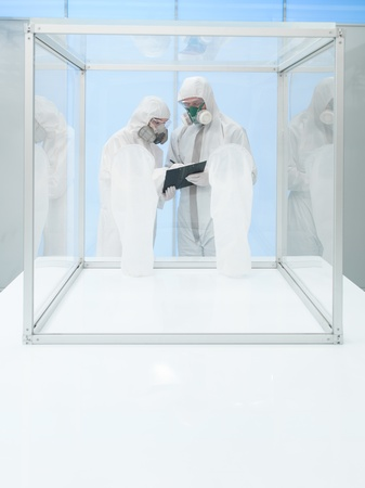 disinfect: two persons in protective suits and breathing masks looking over some data from a clipboard, next to an empty sterile chamber Stock Photo