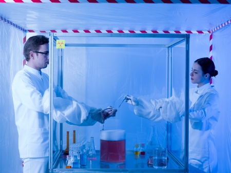 containment: two scientists in a containment tent, a man and a woman, experimenting on a dead animals head with liquid substances in a sterile chamber Stock Photo