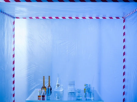containment: different glass containers filled with differently colored liquids on a glass table in a containment tent, lit by a blue light