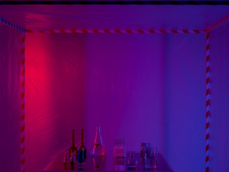 containment: different glass containers filled with differently colored liquids on a glass table in a containment tent, lit by a gradient red, purple and blue light