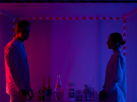 containment: two persons, a man and a woman, standing opposite from each other next to a table with different glass containers in a containment tent, lit by a gradient red, purple and blue light