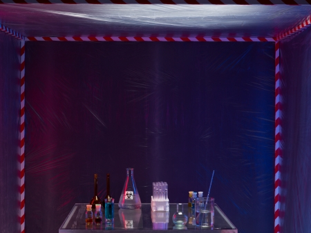 containment: different glass containers filled with differently colored liquids on a glass table in a containment tent, placed outdoors, by night