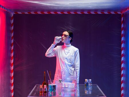 containment: woman scientist in a containment tent, wearing a white lab coat, next to a table with chemicals, smelling a substance from a bottle Stock Photo