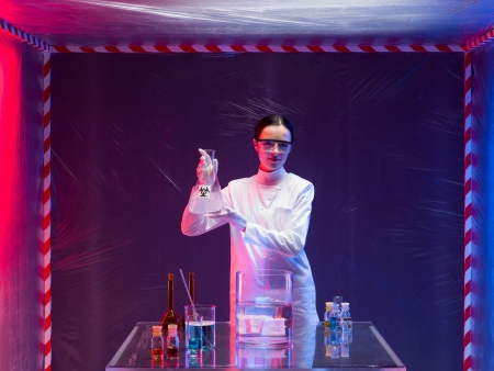 containment: woman scientist wearing a white lab coat and protection goggles holding a bottle labeled as bio hazardous with both hands in front of a table with glassware filled with chemicals, in a containment tent