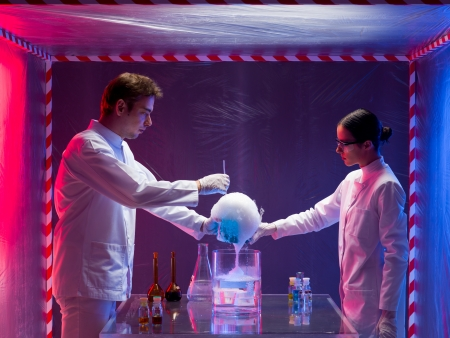 containment: two scientists, a man and a woman, mixing chemicals in a containment tent, holding a glass container filled with a blue substance reacting with abundant foam Stock Photo