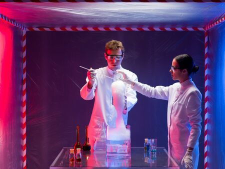 containment: two scientists, a man and a woman, mixing chemicals in a containment tent, holding a glass container with substance reacting with abundant foam Stock Photo