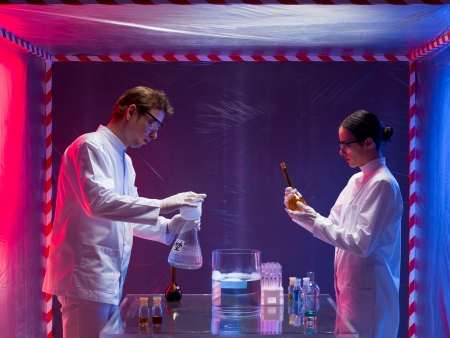 containment: two scientists, a man and a woman, working with chemicals in a containment tent Stock Photo