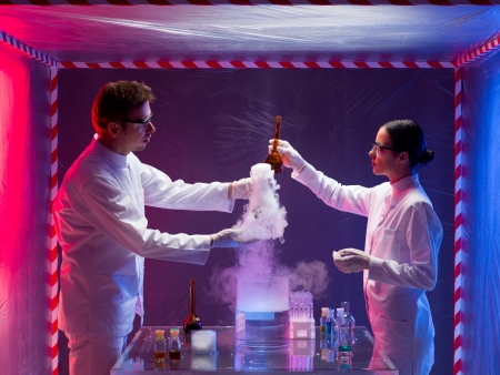 Photograph of a male and female scientists inside a biohazard protective space testing the toxic chemicals while the smoke coming out. photo