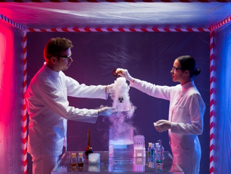 containment: two scientists, a man and a woman, mixing chemicals in a containment tent, holding a glass container labeled as bio hazardous filled with white pouring steam