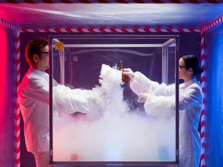 containment: two scientists, a man and a woman, mixing chemicals in a sterile chamber labeled as bio hazardous filled with white steam, the woman holding a brown bottle, in a containment tent Stock Photo