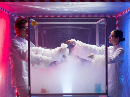 containment: two scientists, a man and a woman, mixing chemicals in a sterile chamber labeled as bio hazardous filled with white steam, in a containment tent