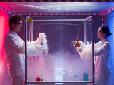 containment: two scientists, a man and a woman, examining results of a chemical reaction in a sterile chamber labeled as bio hazardous filled with white steam, in a containment tent
