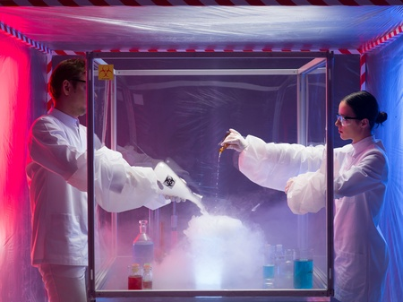 containment: two scientists, a man and a woman, pouring substances into a glass container filled with steam and fumes, in a containment tent