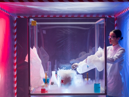 containment: woman scientist conducting experiment with a steaming substance in a protection enclosure, in a containment tent