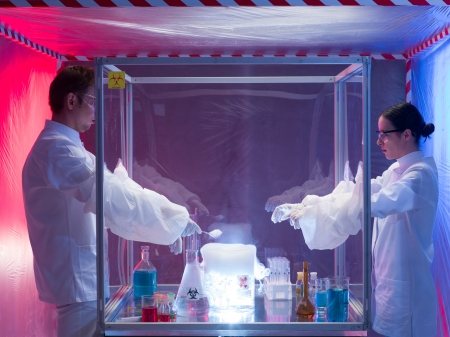 containment: two scientists, a man and a woman, mixing chemicals in a protection enclosure labeled as bio hazardous, into a beaker filled with vapors, in a containment tent