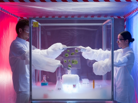containment: two scientists, a man and a woman, conducting experiments with mold cultures in a protection enclosure labeled as bio hazardous, over a beaker filled with vapors, in a containment tent Stock Photo