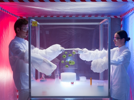 containment: two scientists, a man and a woman, conducting experiments with microorganism cultures in a protection enclosure labeled as bio hazardous, over a beaker filled with vapors, in a containment tent Stock Photo