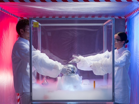 containment: two scientists, a man and a woman, conducting experiments with a disco ball in a protection enclosure labeled as bio hazardous, over a beaker filled with vapors, in a containment tent