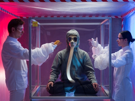 quarantine: a person inside a protection enclosure, wearing a gas mask, being analyzed by two scientists, a man and a woman, the man holding a digital counter and the woman holding a syringe