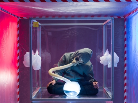 containment: a person inside a protection enclosure, wearing a gas mask, breathing vapors from a bowl filled with a steaming substance in front of them, inside a containment tent
