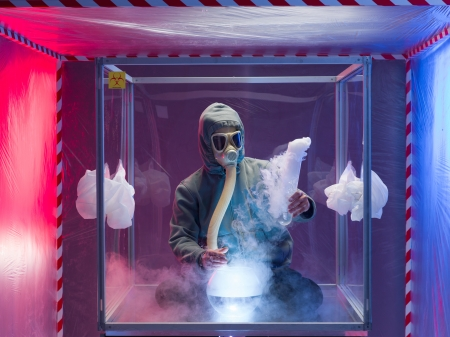 quarantine: a person inside a protection enclosure, wearing a gas mask, conducting experiments with steaming reactions, inside a containment tent