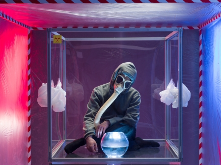 containment: a person inside a protection enclosure, wearing a gas mask, with a bowl filled with a liquid transparent colorless substance in front of them, inside a containment tent