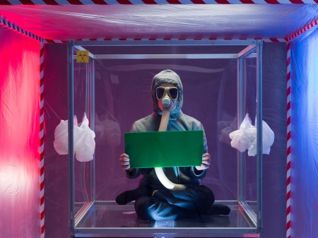 containment: a person inside a protective enclosure, wearing a gas mask, holding a green board with both hands, inside a containment tent Stock Photo
