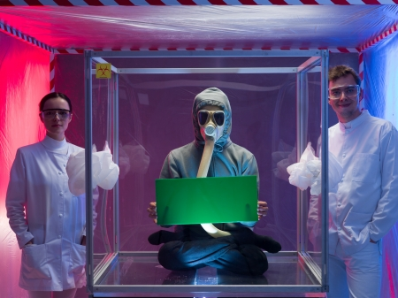 containment: a person inside a protective enclosure, wearing a gas mask, holding a green board with both hands, with two scientists, a man and a woman outside the box, all inside a containment tent