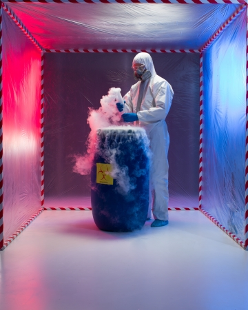 person in a protective suit and gas mask working with steaming substances over a blue waste drum marked as bio hazardous inside a containment tent photo
