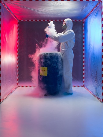 hazardous waste: person in a protective suit and gas mask working with steaming substances over a blue waste drum marked as bio hazardous inside a containment tent