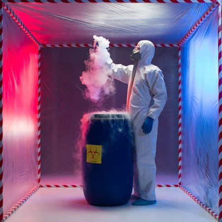 vapour: Laboratory technician working with a biohazardous sample inside an isolation tent which he has drawn from a drum spewing out a white vapour Stock Photo