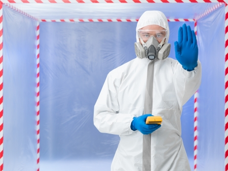 containment: Person in biohazard suit calling a halt by raising a hand in the air while standing in front of a containment tent holding a digital counter or tester Stock Photo